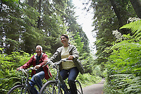 Senior man and middle-aged woman riding bicycles in forest smiling