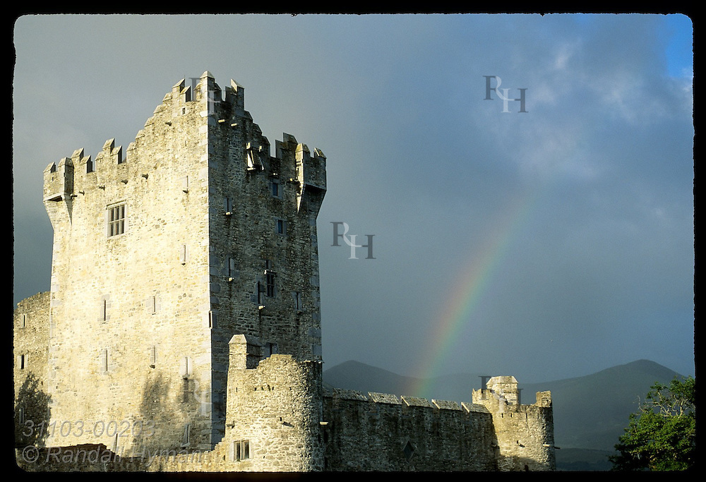 Early morning rainbow glows behind 15th-century Ross Castle on Lough Leane in Killarney National Park, Ireland.