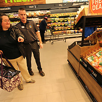 Christie McAllister, of Nettleton, receives help from Jarrod Watts, the ALDI store manager as she shops during the stores grand opening on Wednesday in Tupelo.