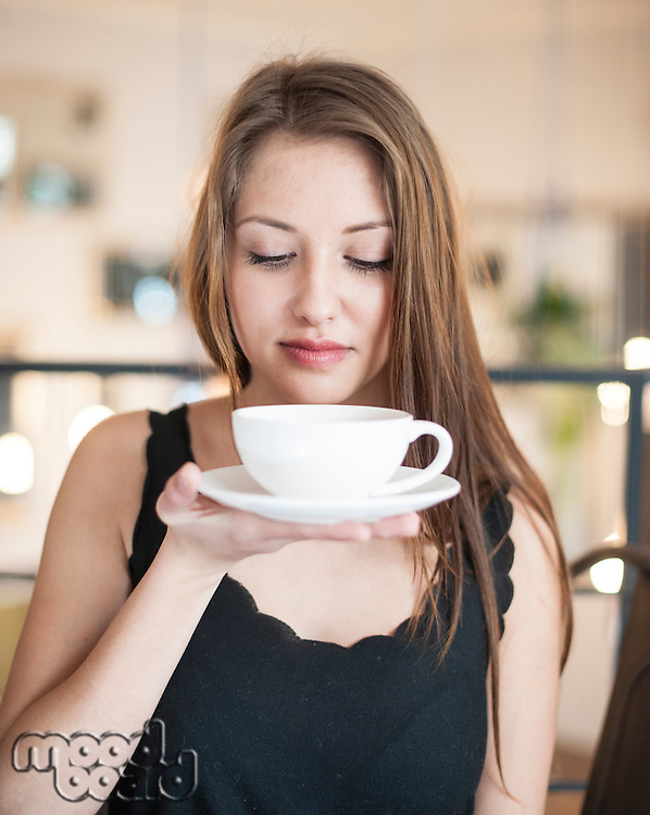 Beautiful young woman holding coffee cup and saucer at cafe