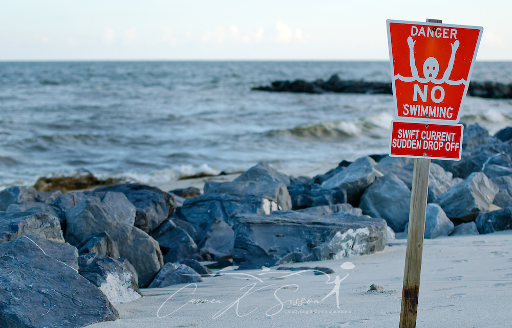 "A ""No Swimming"" sign warns swimmers of swift currents and the danger of rip currents and a strong undertow around the jetties on the east end of Dauphin Island, Ala., Sept. 7, 2012.(Photo by Carmen K. Sisson/Cloudybright)"