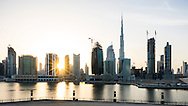 Skyline silhouette of Business Bay and Downtown Dubai as the sun sets behind tall skyscraper office buildings and constriuction cranes. Burj Khalifa and other tower buildings with sunburst of setting sun.