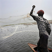 Beninese fisherman work from his pirogues at dawn on the lagoon of Ganvie Cotonou, Benin March 1, 2008..