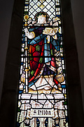 The stained glass Saint Hilda reading the Bible in All Saints church, on 25th September 2017, in Rothbury, Northumberland, England.