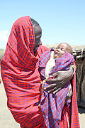Masai father carrying child in his arms, Ngorongoro Conservation Area, Tanzania.