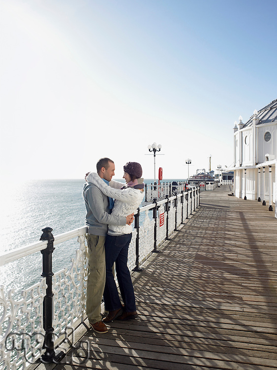 Couple embracing standing on pier side view full length