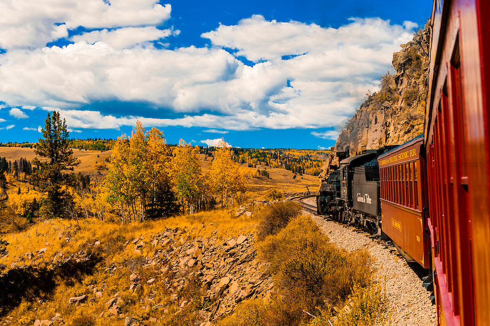 The Cumbres & Toltec Scenic Railroad train pulled by a steam locomotive on the 64 mile run between Antonito, Colorado and Chama, New Mexico. The railroad is the highest and longest narrow gauge steam railroad in the United States with a track length of 64 miles. The train traverses the border between Colorado and New Mexico, crossing back and forth between the two states 11 times. The narrow gauge track is 3 feet wide. It runs over 10,015 ft (3,053 m) Cumbres Pass.