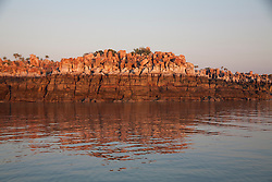 The stunning red of the cliffs of Wailgwin Island is reflected still water.