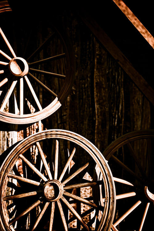 Wooden cart wheels hanging on a shed