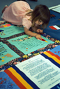 Kira Smith, 2, gets a close-up look at the NAMES Project AIDS Memorial Quilt at Cal Poly University in San Luis Obispo, Calif.