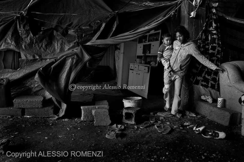 Iraqi Kurdistan, Kawergosk refugee camp. Syrian refugee child are seen as they exit their tent mounted inside an under construction building in the outskirts of Erbil. <br /> ALESSIO ROMENZI