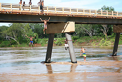 Local kids jump off the bridge at Fitzroy Crossing in the wet season.
