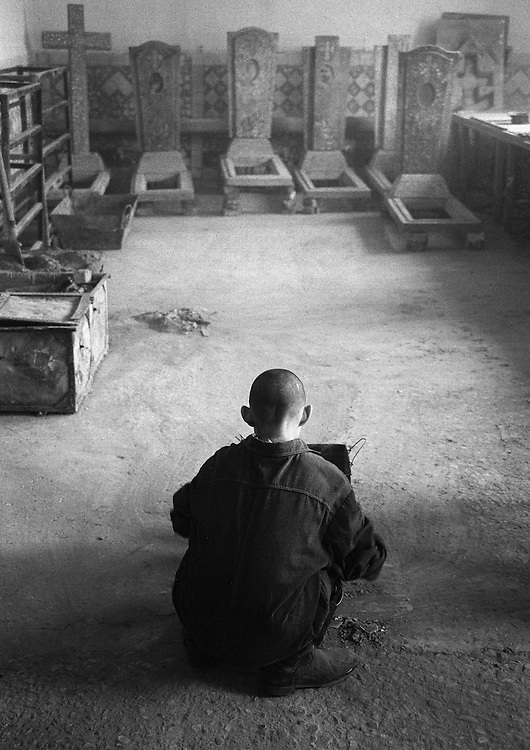 Russian young prisoner works in a small factory where create the tombstones from granite at the colony for prisoner's children in Siberian town Leninsk-Kuznetsky, Russia, 15 January 2001.