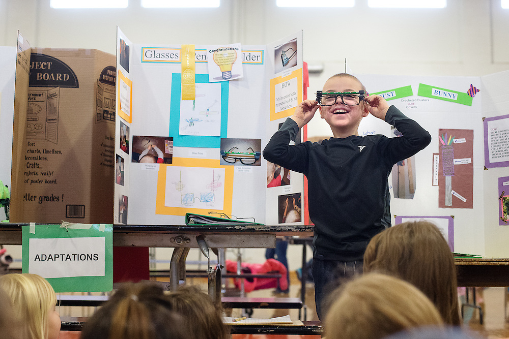 GABE GREEN/Press<br /> <br /> Invent Idaho finalist, Mullan Trail Elementary second-grader Owen Nederhoed, 7, cracks up as he demonstrates his invention, the &ldquo;Glasses Pencil Holder,&rdquo; to his class Friday. Students were presented with the task of creating new products to solve specific problems, were judged on the merit of their invention and the documentation of their process. In preparation for this mandatory activity all second-graders and fourth-grade gifted and talented students learned about the invention process, famous inventors, how to research and how to use computers.