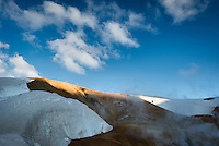Photographer hikes up a hill in Kerlingarfjöll mountain range, central highlands of Iceland.