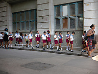 Laughing, uniformed school children on an outing, in a line and holding hands, while walking on a street sidewalk with teachers.