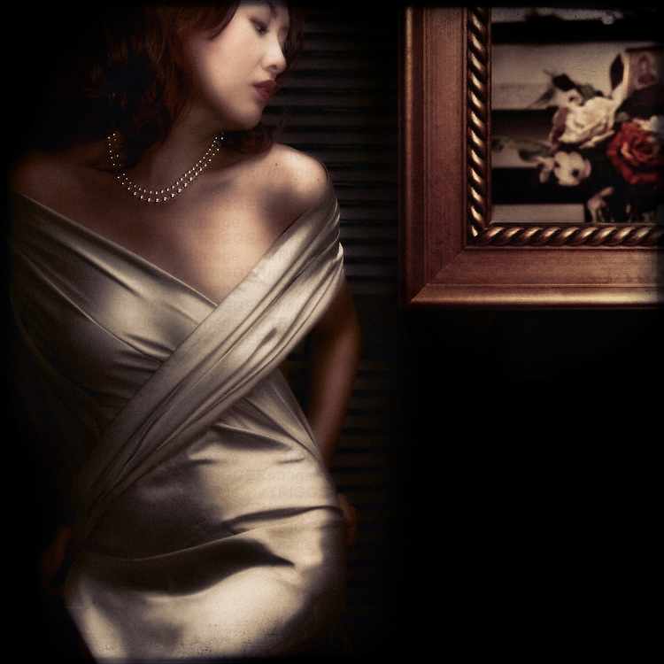 Glamorous young asian woman wearing silk dress and pearl necklace standing beside framed painting