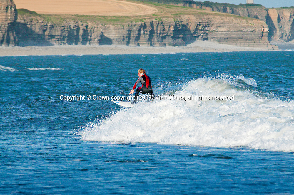 Young boy surfing<br /> Colhuw Beach<br /> Llantwit Major<br /> Glamorgan Heritage Coast<br /> Vale Of Glamorgan<br /> South<br /> Surfing<br /> Activities &amp; Sports