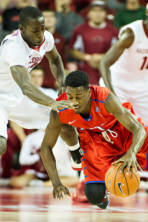 FAYETTEVILLE, AR - NOVEMBER 18:  Ryan Manuel #1 of the SMU Mustangs dribbles the ball from his knees while being guarded by Fred Gulley III #12 of the Arkansas Razorbacks at Bud Walton Arena on November 18, 2013 in Fayetteville, Arkansas.  The Razorbacks defeated the Mustangs 89-78.  (Photo by Wesley Hitt/Getty Images) *** Local Caption *** Ryan Manuel; Fred Gulley III