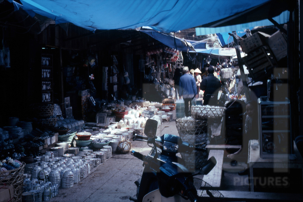 Color film photograph of small street full of crockery sellers in Hanoi, Vietnam, Southeast Asia