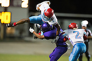 Demarviae Gray (1) of the Carter Cowboys tries to leap over Cam Henderson (9) of the Lincoln Tigers during a high school football game at Forester Stadium in Dallas, Texas on September 18, 2015. (Cooper Neill/Special Contributor)