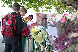 © Licensed to London News Pictures. 19/10/2016. Bell Green, Coventry UK. A seven year old girl has been killed by a truck on Henley Lane, Bell Green, Coventry.  Pictured, School children add flowers to the floral tributes on a fence near the scene. Photo credit: Dave Warren/LNP