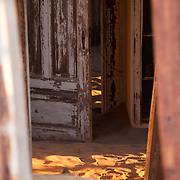 Peering in through the crumbling walls of an old building in Kolmanskop, Namibia