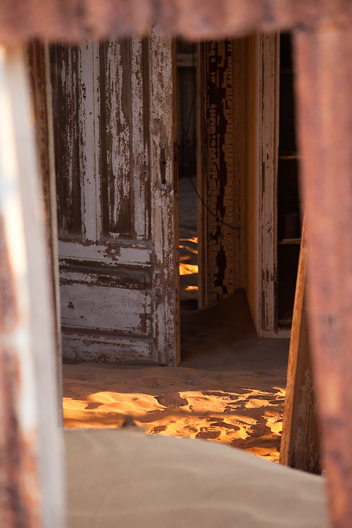 Peering in through the crumbling walls of an old building in Kolmanskop, Namibia