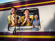 "05 DECEMBER 2013 - BANGKOK, THAILAND:  People lean out the window of a special steam engine train leaving Hua Lamphong Train Station on the 86th birthday of Bhumibol Adulyadej, the King of Thailand. Dec. 5, the King's Birthday, is a national holiday in Thailand, and is also celebrated as the country's ""Fathers' Day."" The State Railways of Thailand put on special trains to take people to the King's ""Summer Palace"" in the oceanside community of Hua Hin where the King granted a public audience. There were also merit making ceremonies throughout the country.  Many people wear yellow on the King's Birthday because yellow is the color associated with his reign. As of 2013, he was the longest reigning monarch in the world.          PHOTO BY JACK KURTZ"