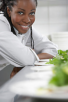 Female chef with plates of salad in kitchen portrait