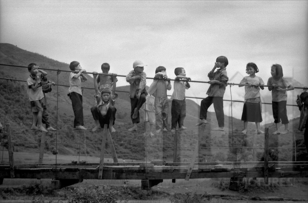 Ethnic minority Lu children climb along the support wires of a pedestrian bridge. They are curious as tourists come into their Hon Village, between Sapa and Binh Lu, Vietnam.(Ethnic minority Lu)