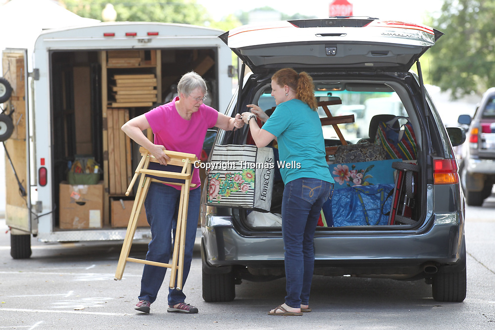 Kathy Flemish, left, helps her daughter, Heather Baumbach of Huntsville unload her for Saturday Gumtree Festival. This is Baumbach's first time to exhibit her art the Gumtree Festival.