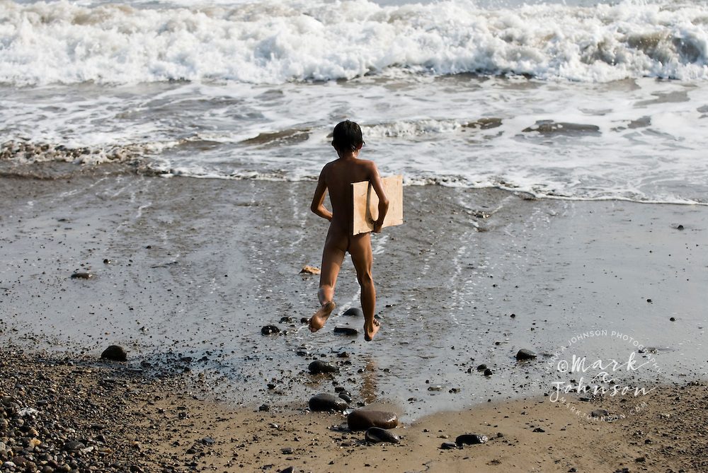 """Boy running on beach with """"surfboard"""", a plywood plank, S. Sumatra, Indonesia"""
