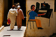 Two women in traditional Moroccan dress stroll past an Internet cafe in the ancient medina of Fes, Morocco on Tuesday afternoon, May 29, 2007. The number of Internet users in Morocco is estimated at 3.5 million and rising. (PHOTO BY TIMOTHY D. BURIDICK)