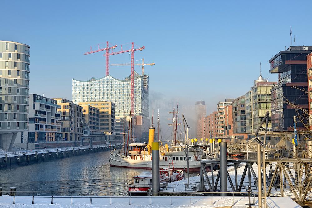 Das Dampfschiff Schaarhörn liegt im Traditionsschiffhafen der Hafencity vor der Elbphilharmonie mit aufziehendem Nebel