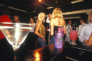 Glamourous looking women at a smart bar surrounded by cocktails, UK 2000's