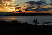 Young lovers silhouetted against sunset over water. Makarska, Croatia