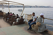 Commuters sit on the top deck of the state-run ferry across the River Nile at Luxor, Nile Valley, Egypt.