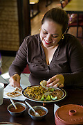 Restaurant owner Lourdes Alvarez having breakfast with her father and uncle at her family's restaurant, Dos Loredos, in Chicago, Illinois.  (Lourdes Alvarez is featured in the book What I Eat;  Around the World in 80 Diets.)    MODEL RELEASED.