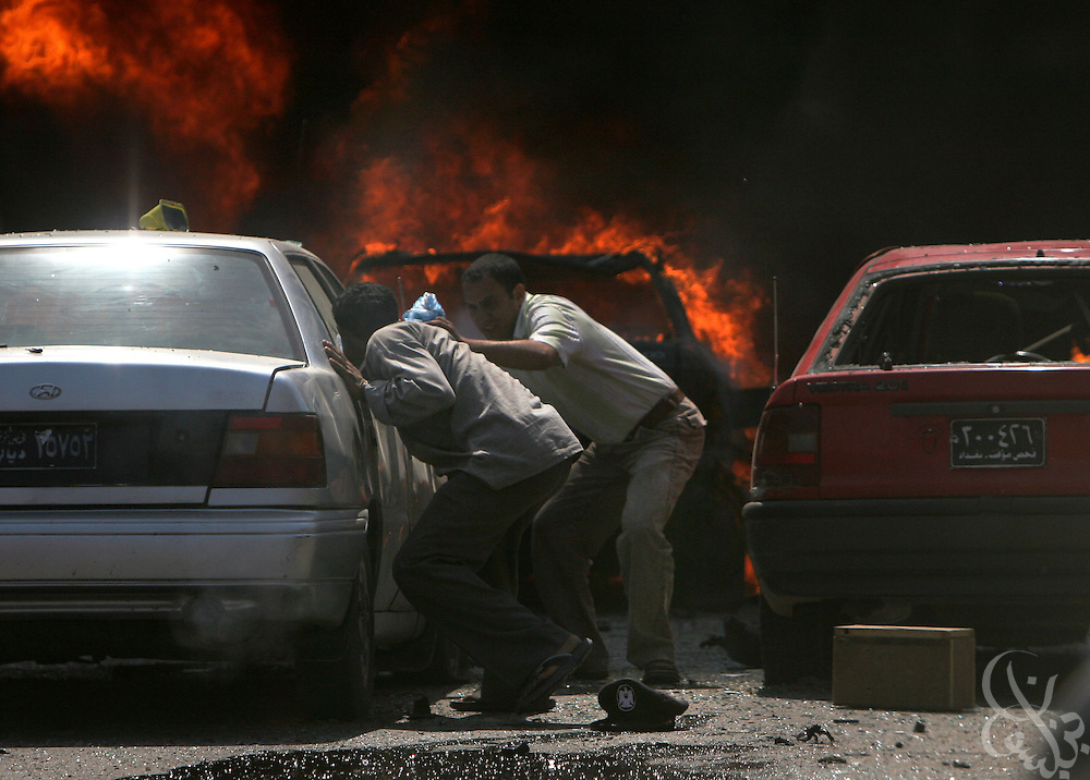 Iraqi men try to push cars away from the flames at the scene of a suicide car bombing in Tahrir square in Baghdad May 07, 2005. The bombing, which targeted a passing civilian contractor convoy, killed at least 6 persons and wounded another 30 during the late morning explosion in the busy commercial area in central Baghdad.