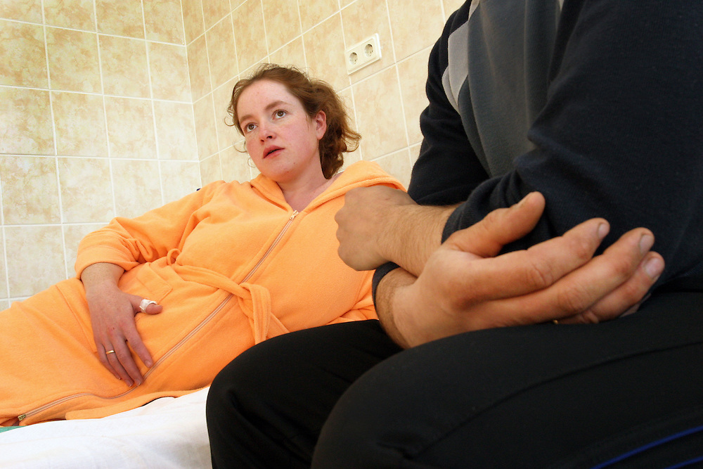 Young woman with husband waiting in hospital during last stages of labour