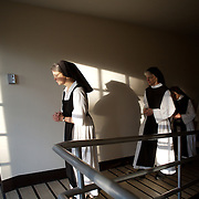 Sister Kathleen O'Neill, followed by Sister Suzanne Mattiuzzo, lead a procession from the chapel to the chapter room at Our Lady of the Mississippi Abbey monastery near Dubuque.   The community of 22 Roman Catholic women follow Jesus Christ through a life of prayer, silence, simplicity and ordinary work.  Their home is a beautiful monastery which sits high on a bluff, overlooking the Mississippi River.