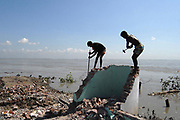 Villagers are shifting their belongings to secure place. The worst flood affected district in Munshigonj on 09 August 2007. People become homeless and suffering shortage of food, drinking water and medicines especially children and woman suffer much more. Rising sea levels and the growing number of natural disasters forced by climate change are already driving migration and displacement. Climate Change is my long-term project where I began to document of marginal condition in my own country of Bangladesh. © Monirul Alam