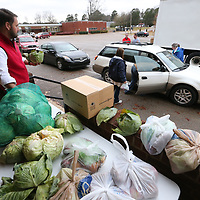 Jay Stanley, left, prepares to pass down another head of cabbage to volunteers distributing food Thursday afternoon from the Baldwyn School District Food Pantry at the Baldwyn Middle School.