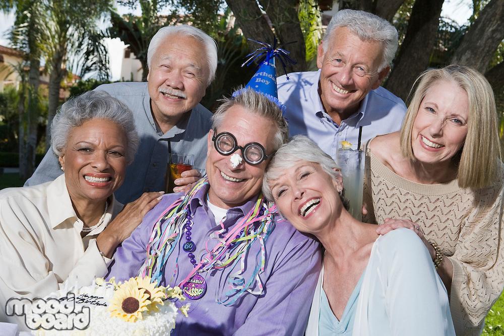 Senior people celebrating birthday in garden, smiling