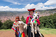 A boy and girl dressed in traditional Peruvian indigenous clothing, stand in front of the city of Cusco.