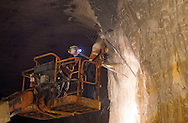Workers on a lift knock down loose material through a process called scaling inside the mine at Pattison Sand Company in Garnavillo, Iowa on June 5, 2013.