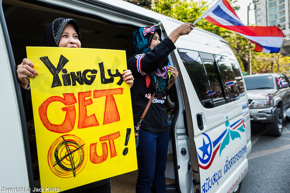 """15 JANUARY 2014 - BANGKOK, THAILAND:  Thai Muslim women lean out a van during a motorcade protest against the Thai government during Shutdown Bangkok. Tens of thousands of Thai anti-government protestors continued to block the streets of Bangkok Wednesday to shut down the Thai capitol. The protest, """"Shutdown Bangkok,"""" is expected to last at least a week. Shutdown Bangkok is organized by People's Democratic Reform Committee (PRDC). It's a continuation of protests that started in early November. There have been shootings almost every night at different protests sites around Bangkok. The malls in Bangkok are still open but many other businesses are closed and mass transit is swamped with both protestors and people who had to use mass transit because the roads were blocked.   PHOTO BY JACK KURTZ"""