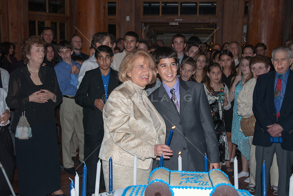 grandmother and her grandson lighting the candles on a cake at a Bar Mitzvah