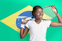 Portrait of young woman with tennis racket against Brazilian flag